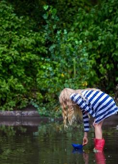 Menina com barco de papel azul em uma poça após a chuva, verão