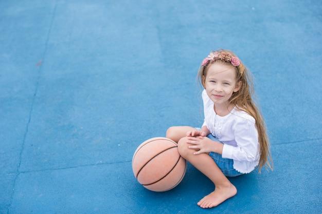 Menina com basquete na quadra ao ar livre no resort tropical