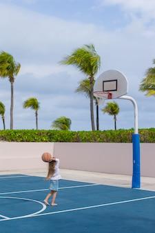 Menina com basquete na quadra no resort tropical