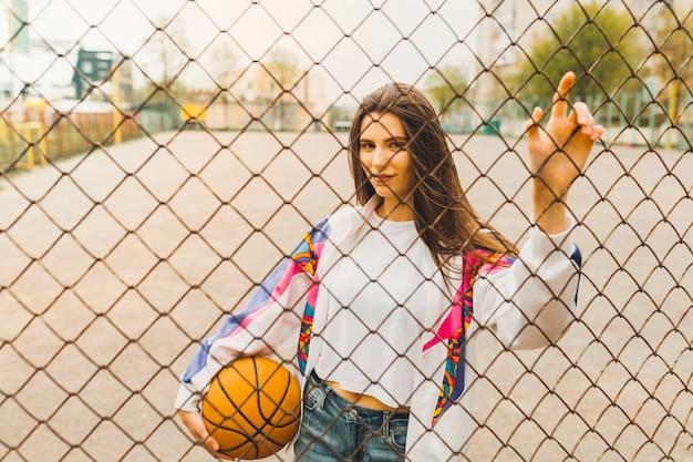 Menina, com, basquetebol, atrás de, cerca