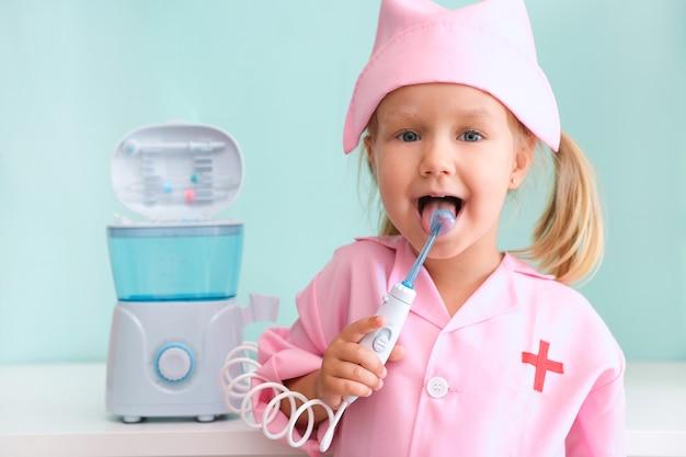Menina com bata de enfermeira limpa a língua com um irrigador. a menina está escovando os dentes com um jato de água de um irrigador.
