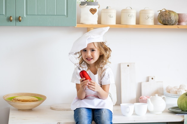 Menina com batedor de ovos na cozinha em casa