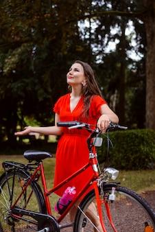 Menina com bicicleta vermelha no parque estica as mãos para a chuva