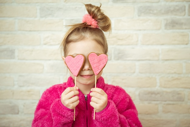 Menina com biscoitos em forma de coração dos namorados nas mãos dela. conceito de amor