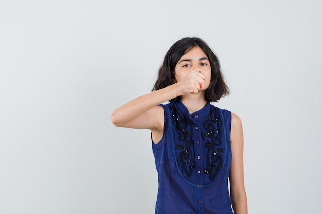 Menina com blusa azul mostrando o punho cerrado para ameaçar e parecendo severa