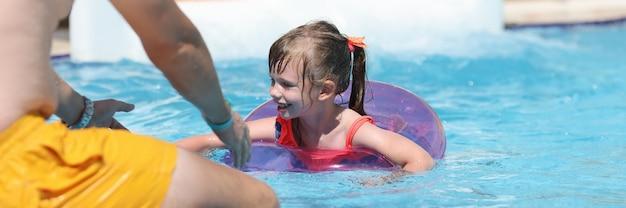Menina com bóia salva-vidas rosa nadando para o pai na piscina do parque aquático