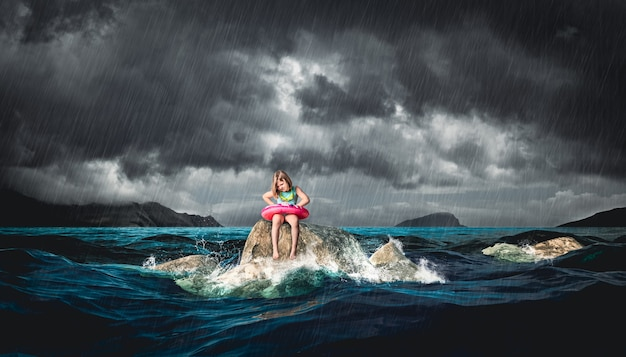 Menina com bóia salva-vidas sentado em uma rocha durante uma tempestade.