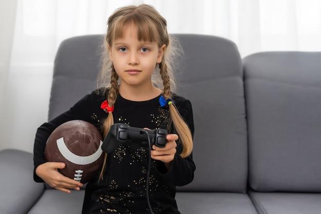 Menina com bola de rúgbi e joystick para jogar videogame em casa