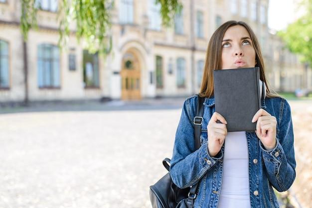 Menina com bolsa e livro olhando o fundo do campus