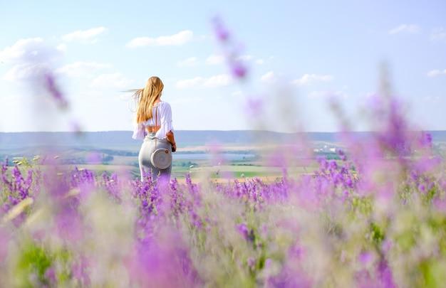Menina com bolsa em saia e blusa branca no campo de lavanda no verão