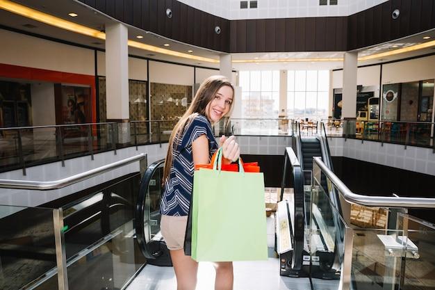 Menina com bolsas de papel gesticulando no shopping