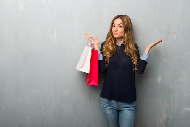 Menina, com, bolsas para compras, tendo, dúvidas, enquanto, levantamento, mãos ombros