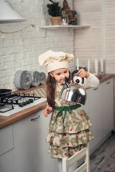 Menina com boné de chef examina uma chaleira na cozinha