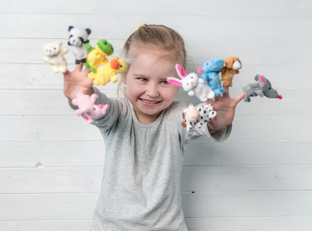 Menina com bonecos de boneca nas mãos dela