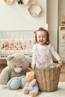 Menina com brinquedos no quarto das crianças