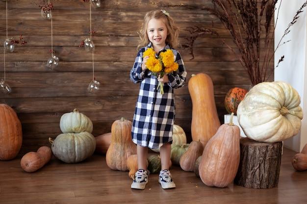 Menina com buquê de flores amarelas de outono em casa