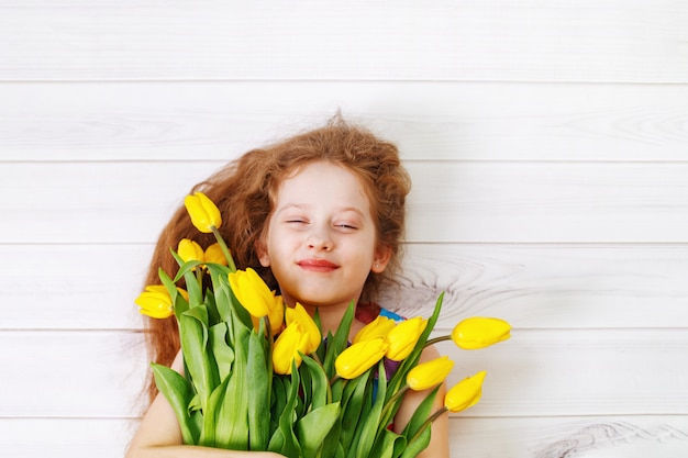 Menina com buquê de tulipas.