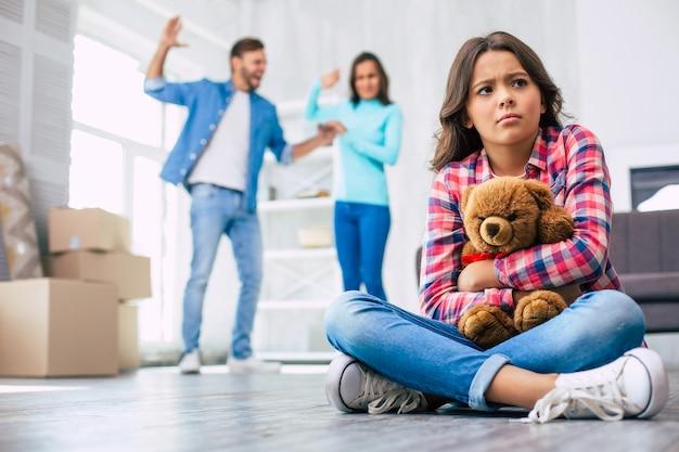 Menina com cabelo castanho cacheado está sentada no chão, abraçando um ursinho de pelúcia, parecendo perturbada com os pais brigando no fundo. conceito de mudança de casa