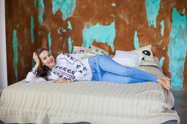Menina com cabelo castanho deitada na cama