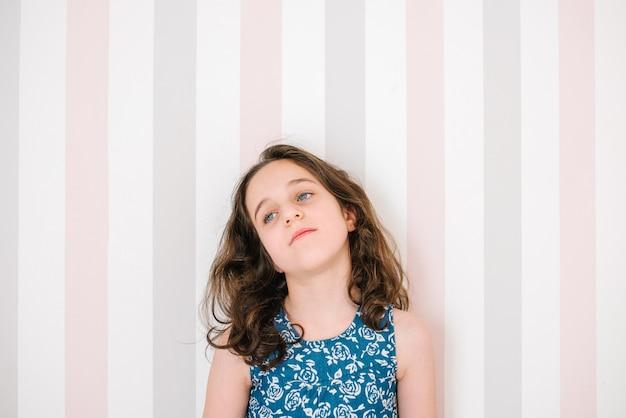 Menina com cabelo castanho e olhos azuis está pensando em seu quarto.