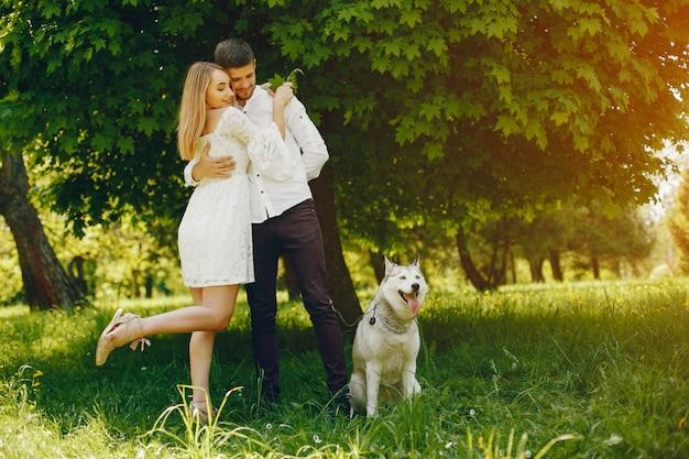Menina com cabelo claro e um vestido branco em uma floresta ensolarada com seu namorado e cachorro