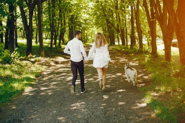 Menina com cabelo claro vestido de branco está jogando junto com seu cachorro e namorado