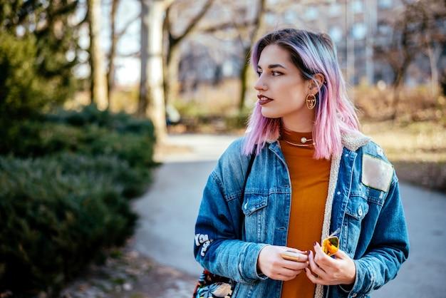 Menina com cabelo colorido, esperando por alguém no parque.