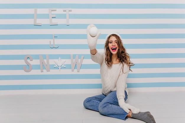 Menina com cabelo comprido e encaracolado e batom brilhante posando de brincadeira, jogando uma bola de neve em direção a