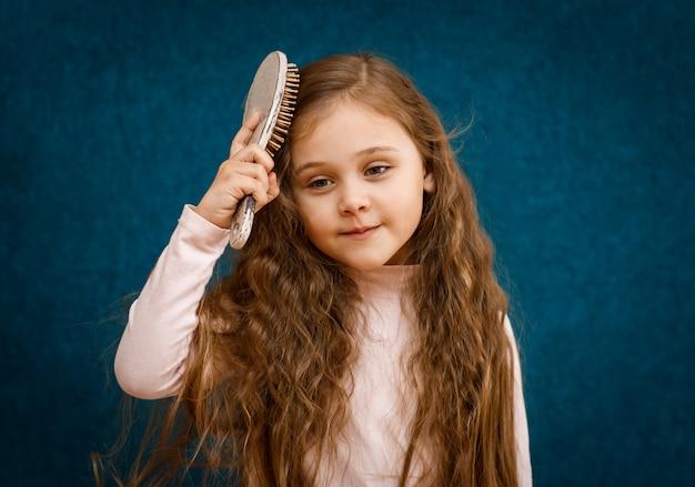 Menina com cabelo comprido é penteada por um pente