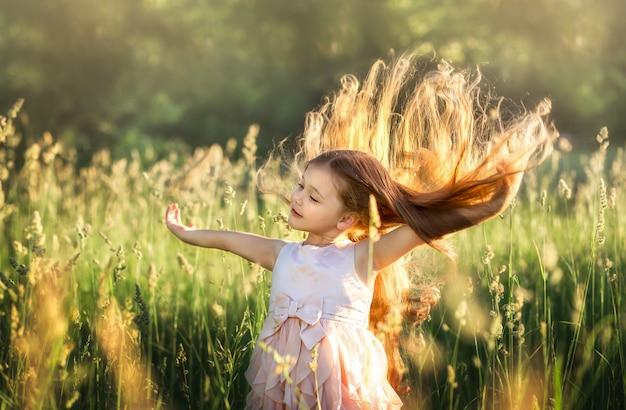 Menina com cabelo comprido em um lindo vestido sobre a natureza no verão