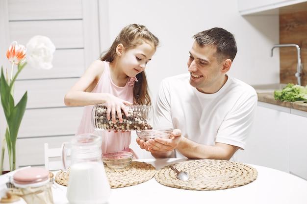 Menina com cabelo comprido. pai e filha juntos. a família se prepara para comer.