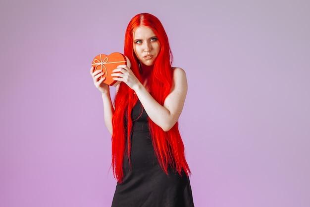 Menina com cabelo comprido ruivo segurando uma caixa de presente no fundo rosa