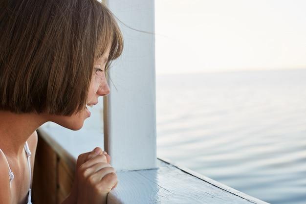 Menina com cabelo cortado, tendo a viagem do mar no navio, olhando do convés, assistindo o mar com olhar animado