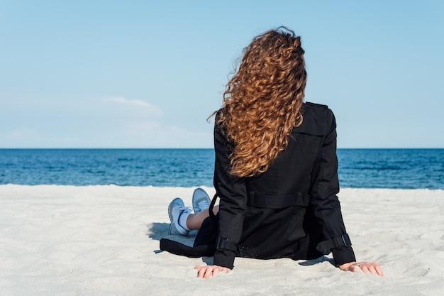 Menina com cabelo encaracolado bonito sentado na praia em um casaco e olhando para o mar