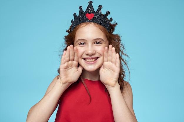 Menina com cabelo encaracolado com uma coroa na cabeça vestido vermelho estilo de vida azul