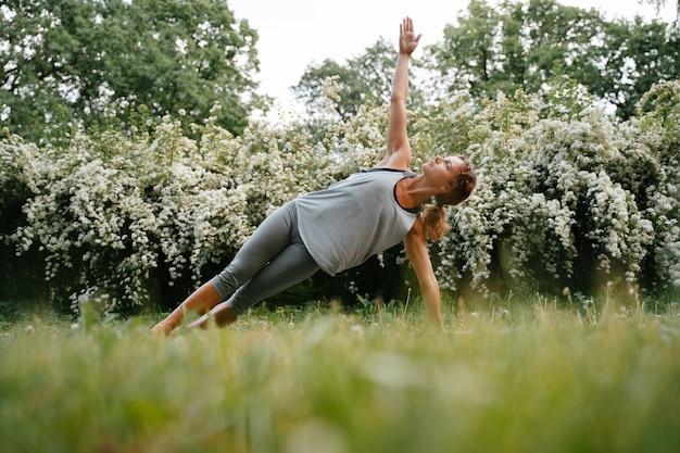 Menina com cabelo encaracolado esguio praticando ioga ao ar livre pela manhã alongamento e equilíbrio nos esportes