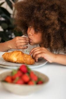 Menina com cabelo encaracolado tomando café da manhã
