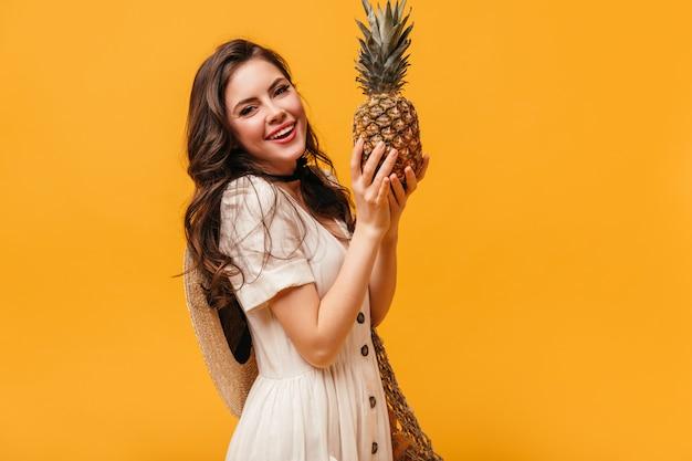 Menina com cabelo escuro ondulado está sorrindo e segurando o abacaxi em fundo laranja.