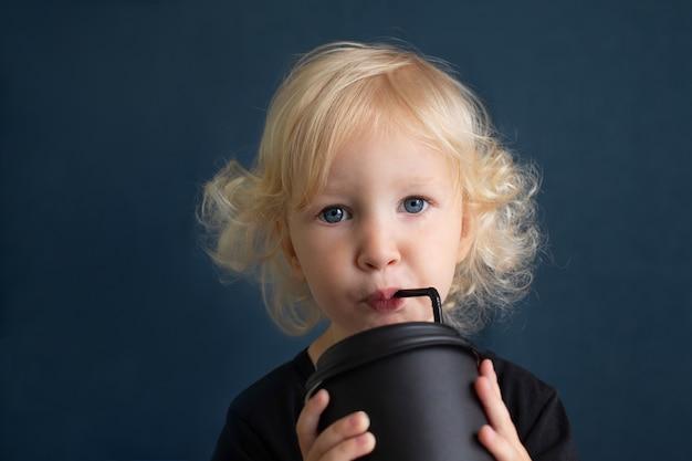 Menina com cabelo loiro encaracolado bebendo em um grande copo preto de bambu reutilizável com canudo