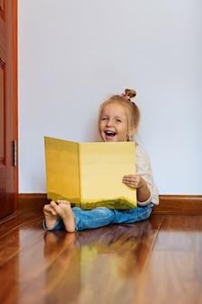 Menina com cabelo loiro, lendo o livro em casa