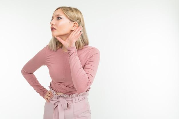 Menina com cabelo loiro ouve uma conversa sobre um fundo branco com espaço de cópia.