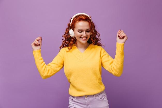Menina com cabelo ondulado dançando em fones de ouvido na parede lilás
