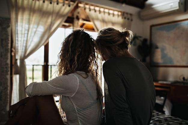 Menina com cabelo ruivo cacheado, vestida com blusa branca, está descansando com o homem em casa