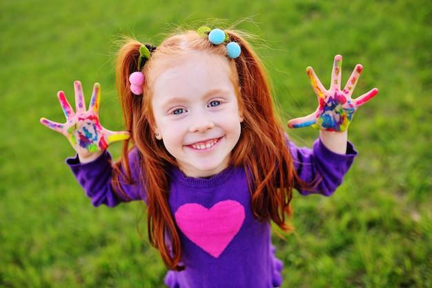 Menina com cabelo vermelho mostra as mãos sujas com tintas multicoloridas e sorrisos