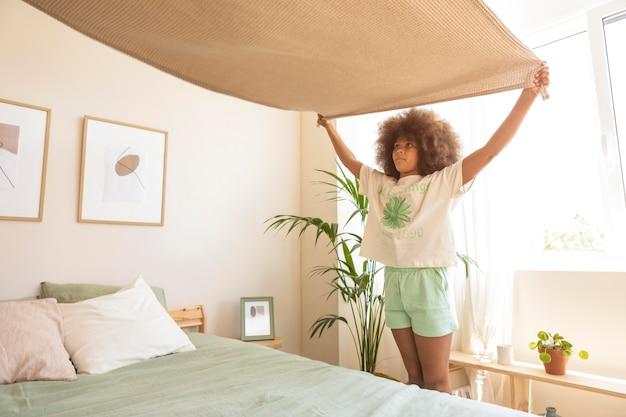 Menina com cabelos cacheados fazendo a cama