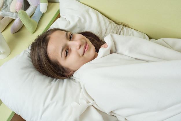 Menina com cabelos castanhos compridos, dormindo em um travesseiro na cama