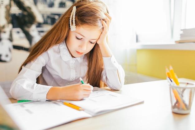 Menina com cabelos longos, estudando ou concluindo o trabalho em casa sobre uma mesa com pilha de livros e pasta de trabalho