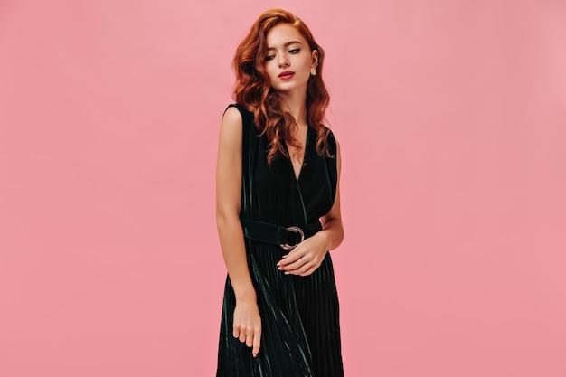 Menina com cabelos ondulados, vestidos com roupas de veludo, poses na parede isolada