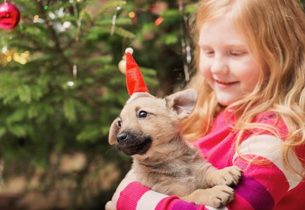 Menina com cachorrinho na árvore de natal ao fundo