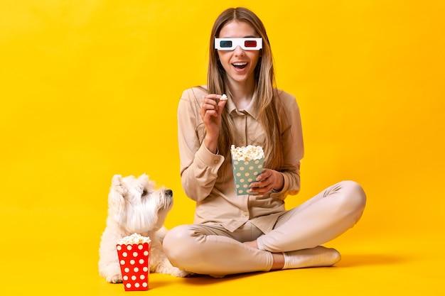 Menina com cachorro assistindo filme com pipoca em fundo amarelo. foto de alta qualidade